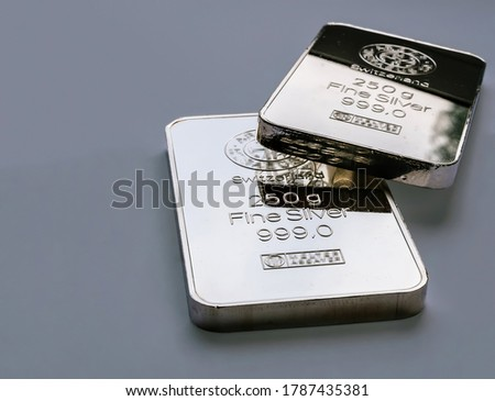 Two minted silver bars weighing 250 grams each on a gray background. Selective focus. Royalty-Free Stock Photo #1787435381