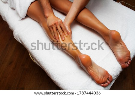 Lymphatic drainage massage of legs and lower legs. Female feet in the hands of a masseur. #1787444036