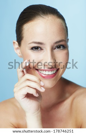 Portrait of young woman applying moisturizer #178746251
