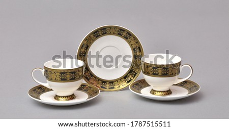 A set of coffee and tea cups, mugs and  plates on a gray background.