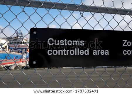 A black and white fence with a sign attached to a chain link industrial boarder. It has customs controlled area in white text. There's a harbour with a wharf in the background under a blue sky.