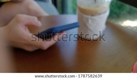 A woman's hand is using a mobile phone to search for information and ideas for working and shopping online blurred picture for background.