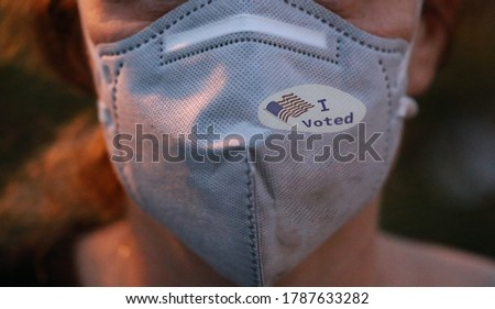 Selective focis on I Voted sticker with USA flag on face mask on caucasian female after voting for president for President #1787633282
