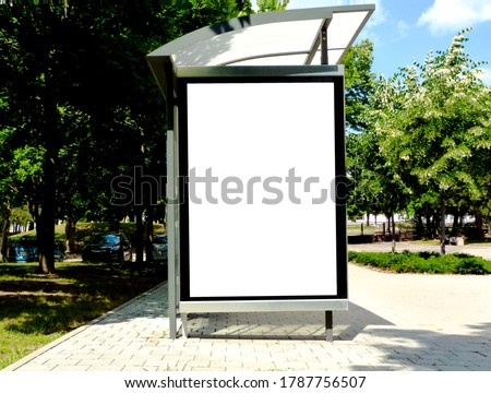 image composite of bus shelter at bus stop of blank light box and glass structure. park-like urban setting. green background. safety glass design. white poster ad commercial poster space display glass #1787756507