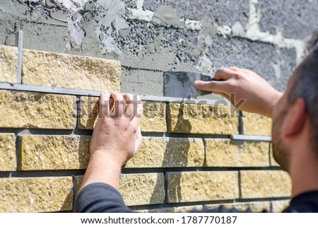 Man decorates the facade of the fence with decorative torn bricks, close up view. Work at home during quarantine, DIY Royalty-Free Stock Photo #1787770187