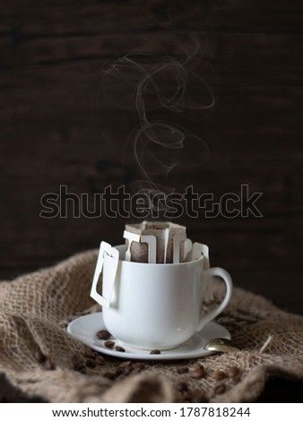 Hot Drip Coffee with Steam. Drip Coffee Still Life, Rustic Country Lifestyle. Espresso with Coffee Beans on Dark Background with Copy Space. Royalty-Free Stock Photo #1787818244
