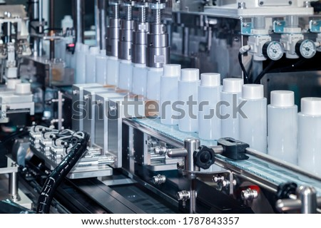 white plastic bottle moving on conveyor belt of auto capping and labeling machine at cosmetic and skin care manufacturing. cosmetic industry and ai technology machinery concept. #1787843357