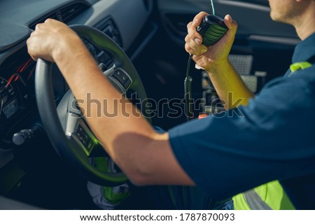 Cropped photo of a man in workwear with a two-way radio transceiver sitting in a vehicle Royalty-Free Stock Photo #1787870093