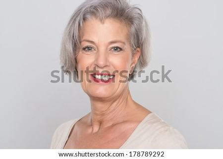 Smiling senior woman in front of grey background #178789292