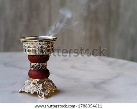 Ornate Arabian Bakhoor incense burner censer emitting white smoke. With copy space Royalty-Free Stock Photo #1788054611