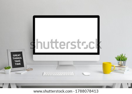 Computer display mockup. Web design presentation template. Modern studio work desk with plant, picture frame, keyboard, mouse, coffee mug and books.