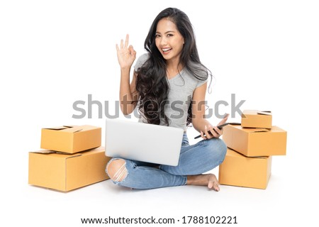 Isolated  Portrait of an Asian woman sits on the floor with a lot of boxes beside She uses a laptop and a smartphone to buy products and services from home. Shop online concept. She smiled and okay.  #1788102221