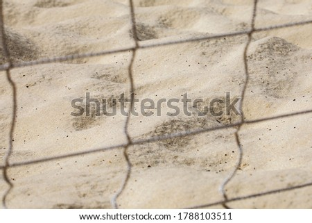 sand with a shade from a beach volleyball net on it on a bright sunny day #1788103511