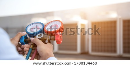 Technician using manifold gauge is measuring equipment for filling industrial factory air conditioners and checking maintenance outdoor air compressor unit. Royalty-Free Stock Photo #1788134468