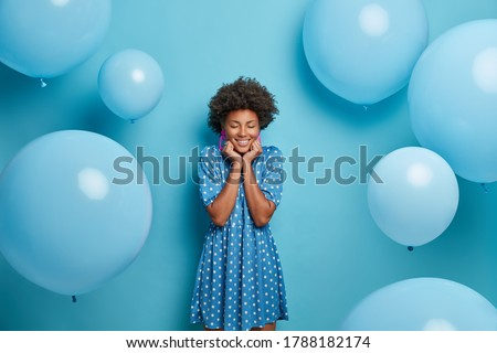 Smiling glad dark skinned woman enjoys birthday party, stands with eyes closed and charming smile, wears fancy blue polka dot summer dress, waits for guests poses around inflated balloons, makes photo #1788182174