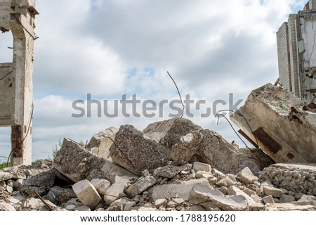 Grey concrete fragments of the Foundation against the background of a destroyed building against the sky. Background. Royalty-Free Stock Photo #1788195620