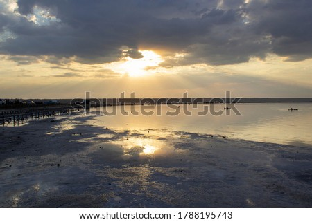 Dark dramatic stormy sky with golden summer sunset and sun light going through clouds with calm sea water reflection #1788195743