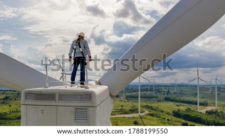 Windmill engineer wearing PPE standing on wind turbine Royalty-Free Stock Photo #1788199550