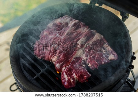 Dry-aged Angus premium meat, Skirt Steak grilling on a kamado grill. Grilling beef meat. Barbecue Meat close upon a grill.  Homemade premium beef grilling. Read meat on the grill. Natural light food  #1788207515