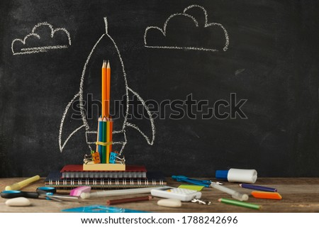 Rocket from stationery on desk and background of chalkboard. Children imagination and creativity. Back to school.