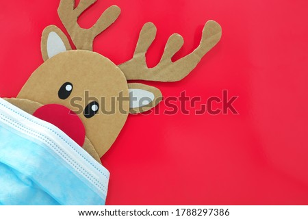 Cardboard cutout of a red-nosed reindeer peeking while wearing a face mask. Covid during Christmas season concept. Red background with copy space. #1788297386