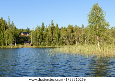View over a little lake with a cabin at the shore and a house on a hill against a blue sky in background, picture from Vasternorrland, Sweden.