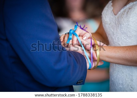 Close up picture of bride and groom's hands tied with colorful blue, purple and yellow ribbons, white lace wedding dress, dark blue suit