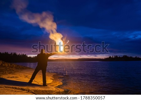 Smoke signal. A man with a smoke torch in the evening by the water. Rescue. SOS. Distress signal. The man lights a smoke signal and calls for help. A man in a life jacket on the lake shore. Royalty-Free Stock Photo #1788350057