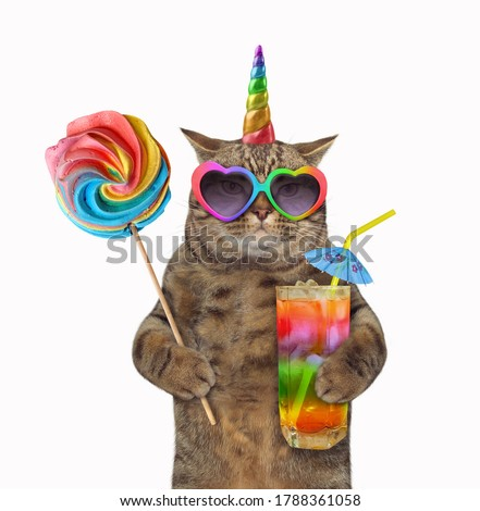 The beige cat unicorn in sunglasses  is holding a lollipop and a glass of rainbow juice with a straw drinking. White background. Isolated.
