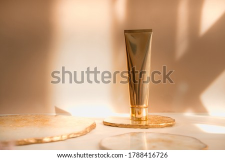 Golden cosmetic tube light pastel color background, lights and shadows. Natural minimalism look, clean concept. Minimal styling, still life. Beauty blogging, branding layout,  skin care ad mock up #1788416726