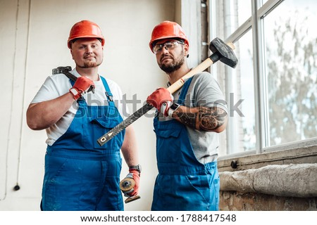 Workers, looking at the camera, standing at the construction site. They are wearing red safety helmets and one of them is holding a sledgehammer for repairs. Royalty-Free Stock Photo #1788417548
