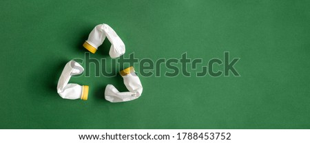 White recycle sign created of plastic bottles on green background flat lay with copy space. PET recycling concept.