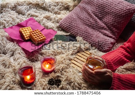 Female hands holding a mug of hot tea. Autumn.Home.Warmth. Comfort. a Cup with a hot drink in women's hands, dessert and candles on the background of a cozy blanket. Autumn cozy evening by candlelight #1788475406