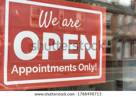 outdoor sign showing pandemic services during virus. Text on vintage red sign 'We are OPEN Appointments Only!' A business sign stating OPEN hanging door at the hairdresser or beautician. Hair dresser.