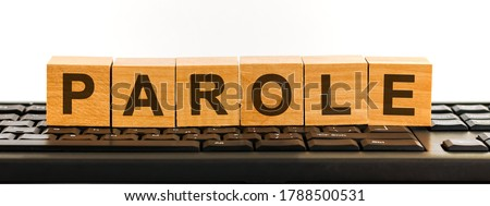 PAROLE word made with building blocks. A row of wooden cubes with a word written in black font is located on a black keyboard.