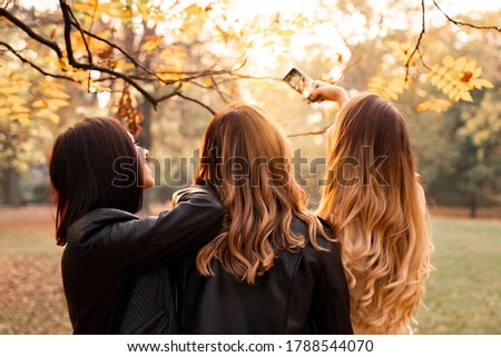 ladies , with beautiful hair styles, taking picture of them in park in fall season