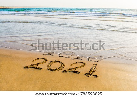 Happy New Year 2021 text on the sea beach. Abstract background photo of coming New Year 2021 and leaving year of 2020 Royalty-Free Stock Photo #1788593825