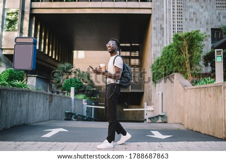 Youthful African American male wearing backpack and eyeglasses walking in modern city district and carrying mobile phone and coffee cup while looking away #1788687863