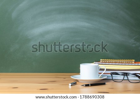 Stacked notebooks and cup of coffee on wooden school desk with a green chalkboard. The blank blackboard in the background for copyspace