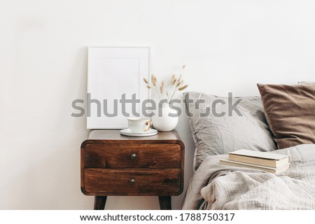 White frame mockup on retro wooden bedside table. Modern white ceramic vase with dry Lagurus ovatus grass and cup of coffee. Beige linen and velvet pillows in bedroom, Scandinavian interior.