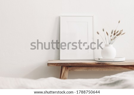 White frame mockup on vintage wooden bench, table. Modern white ceramic vase with dry Lagurus ovatus grass and marble tray. Blurred beige linen blanket in front, Scandinavian interior. Royalty-Free Stock Photo #1788750644