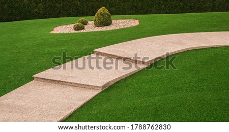 Front yard with garden path and outside staircase made of granite and artificial turf Royalty-Free Stock Photo #1788762830