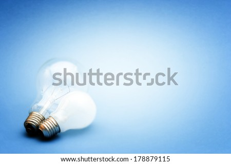 Background with lit lightbulb. Isolated on blue #178879115