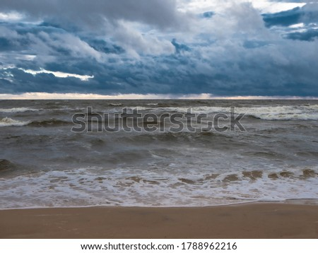 Sea beach during a thunderstorm with large dark rain clouds, soft picture