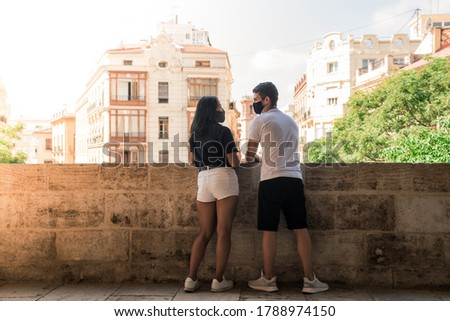 Lovely couple looking to each other wearing facial mask to prevent coronavirus, on a sunny day at a historic building of Valencia center. Concept of sightseeing during covid in Spain. Royalty-Free Stock Photo #1788974150