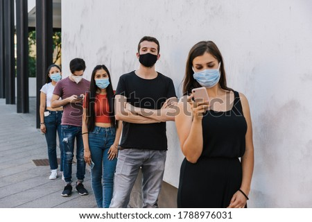 Group of young people at safety distance near a white wall in queue in protection by Coronavirus, Covid-19 with face mask while using the device - Multiracial group of friends - Concept of security Royalty-Free Stock Photo #1788976031
