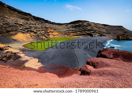 """Lago Verde (""""Green Lake"""") or Charco de Los Clicos in El Golfo, Lanzarote, Canary Islands, Spain. Uniquely colorful landscape with black sand beach, dark volcanic rocks and red earth.  Royalty-Free Stock Photo #1789000961"""