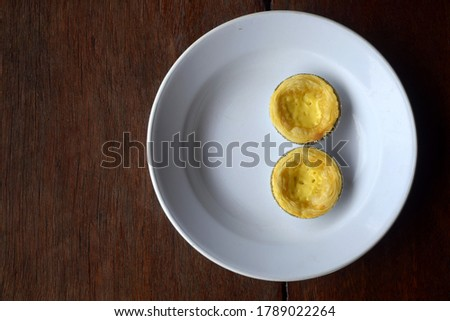 this pic shows egg tart on white dish with wooden background, home cooking food concept