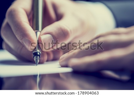 Retro effect faded and toned image of a man writing a note with a fountain pen. Royalty-Free Stock Photo #178904063
