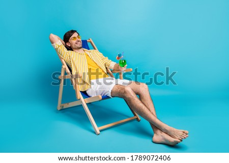 Full size photo positive guy enjoy rest relax exotic resort sun bathing hold glass cocktail sit deckchair wear white yellow striped shirt shorts barefoot isolated blue color background